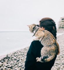 Young woman with cat standing on pebble coastline near the sea.