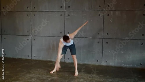 a man stands barefoot on the bare floor and performs an