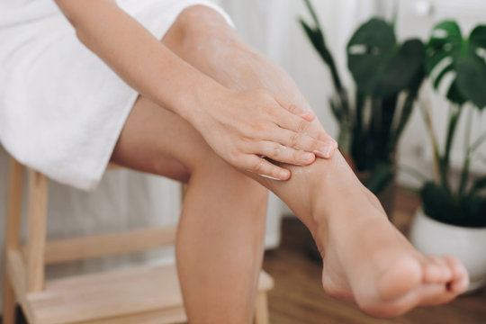 Skin care and wellness concept. Girl hand with moisturizer cream smearing legs for soft skin result. Young woman applying cream on her legs after shaving in bathroom with green plants.