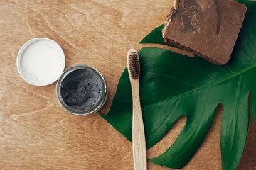 Natural toothpaste activated charcoal and bamboo toothbrush on wooden background with green monstera leaf. Plastic free beauty essentials, teeth care. Zero waste concept. Sustainable lifestyle.