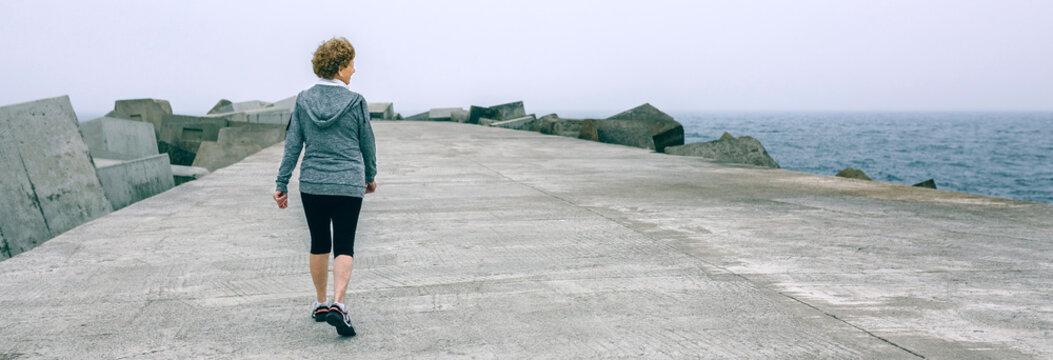 Back view of woman walking by sea pier