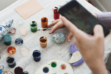 Hands holding phone and taking photo of stylish easter flat lay of painting egg on rustic table with paint,brushes, bird toy. Easter workshop.Decorating easter egg, holiday preparations.