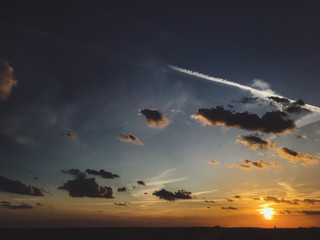 Beautiful amazing sunset, view of city and sky. Blue and yellow sky with sun and clouds, atmospheric scene of evening or morning. Dusk or dawn. Copy space