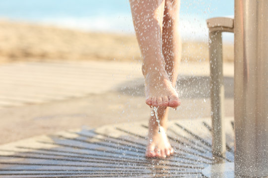 Woman cleaning feet in a shower after beach day