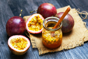 fresh passion fruit juice in glass bottle wooden spoon on dark wooden table