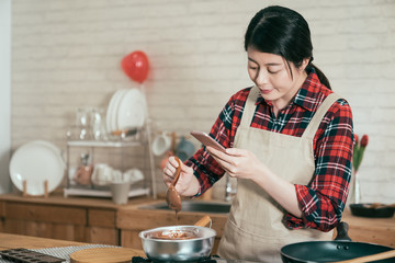 Charming asian woman using mobile gadget records video of cooking process and photographs composition of melting chocolate in pot on stove. young girl handmade cocoa sweet dessert on valentine day.