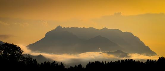 orange mountain silhouette background with kaisergebirge peak, tyrol