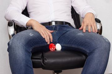 A man in a white shirt sits in an office in a chair whose varicocele of the spermatic cord, urology, pain