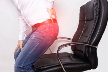 A man in the office holding his back from a chair, the concept of back pain, intervertebral hernia and osteochondrosis of the spine