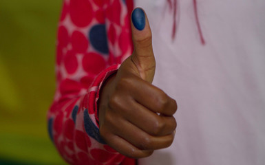 A voter shows off her inked thumb after casting a vote in Kigali