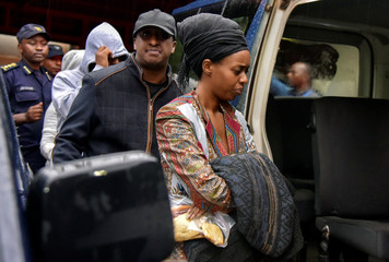 Diane Shima Rwigara, a leading critic of Rwanda's president, is escorted by her family members after she was arrested by police in Kigali