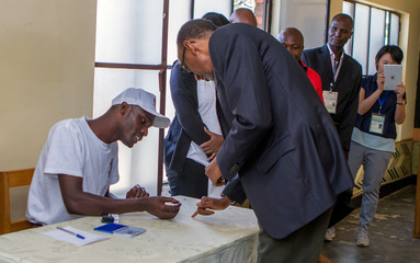 Rwandan President Paul Kagame get his finger inked by polling assistant after casting a vote in Kigali, Rwanda