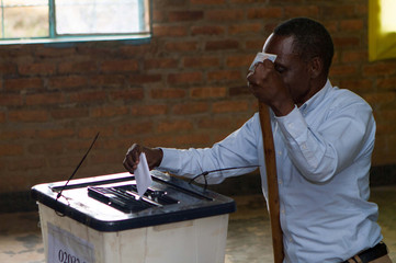 A disabled man casts his vote at a polling station in Kigali