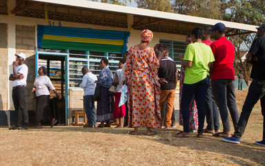 People queue as they wait to cast their votes at a polling station in Kigali