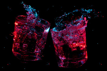 Big splashes of liquid glowing in colorful lights in two rocks glasses clinking in toast isolated on a black background