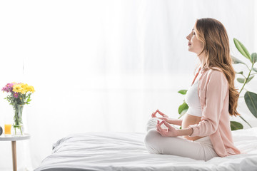 Side view of pregnant woman meditating with closed eyes