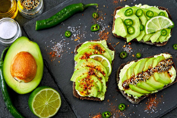 Healthy avocado toasts with spices, lime and chili, presented on a gray stone board.