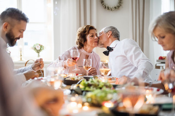 A senior couple sitting at a table on a indoor birthday party, kissing. Wall mural