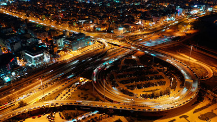 Aerial drone night shot of illuminated ring highway junction near the sea