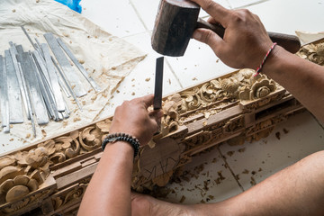 Hands of a carpenter making traditional wood  carving in Bali