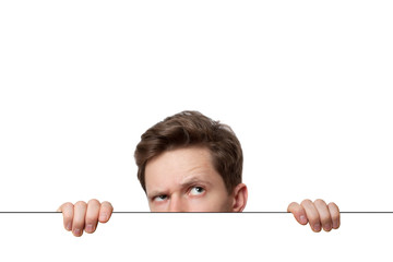 Young man with surprised eyes peeking out from behind billboard paper poster. Man peeking out from the edge and looking at camera isolated on a white background