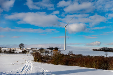 Une éolienne en hiver sur la neige sur un ciel bleu