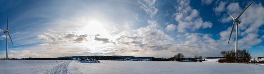 Panoramique avec des éoliennes d'un paysage en hiver avec de la neige sur fond de ciel bleu en Moselle