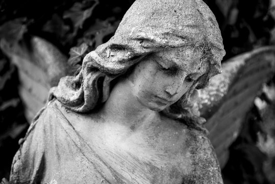 A fragment of ancient sculpture angel in a golden glow in the old cemetery. Symbol of love, invisible forces, purity, enlightenment, ministry. Chariot. Black and white.