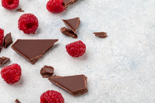 Dark chopping chocolate with fresh raspberries. Top view, copy space, white background.
