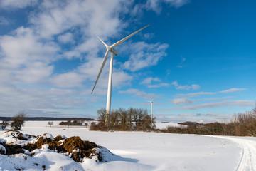 Grande éolienne dans un paysage en hiver avec de la neige sur fond de ciel bleu en Moselle