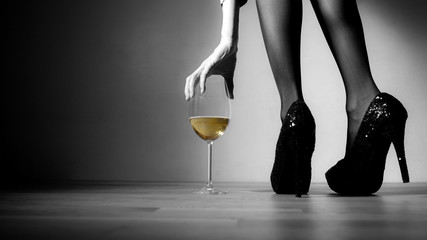 Beautiful girl legs and a glass of alcoholic beverage, black white photo (golden champagne glass)