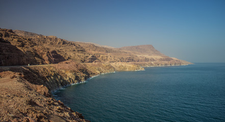 Middle East desert bare mountain ridge in perspective foreshortening along dead sea shoreline, panorama photography