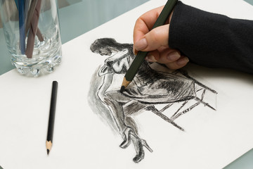 The artist at work. A woman's hand with a pencil draws on a sheet of paper.