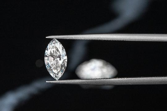 marquise diamond with tweezer on black background