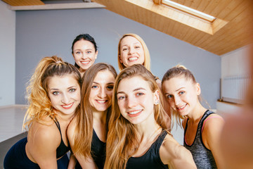 Group of young attractive women dressed in sportswear taking selfie in a sport dance, yoga, pilates studio.