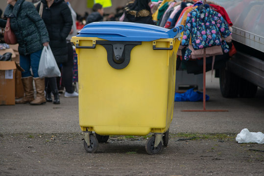 close up of yellow dumpster bin with blue lid and market stall in background