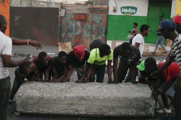 Workers unblock a street after anti-government protests in Port-au-Prince