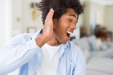 African American man at home smiling with hand over ear listening an hearing to rumor or gossip. Deafness concept.