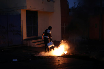 A policeman tries to put out burning garbage used to block a street as part of anti-government protests in Port-au-Prince
