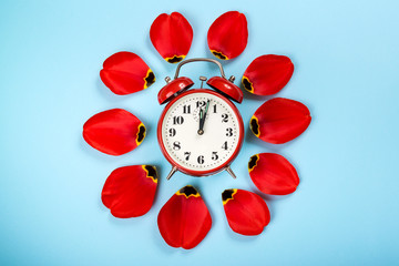 Alarm clock with tulip petals around. Flat lay style, over blue background. Daylight savings time concept. Spring Forward. Stylish vintage alarm clock. Creative spring pattern with space for text.