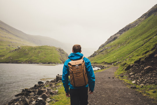 Young Man with a backpack from behind hiking on a trail through fjord in the wild country