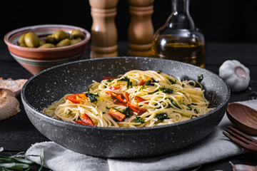 Pan of cooked italian pasta. Traditional spaghetti meal with vegetables and olives on black rustic background