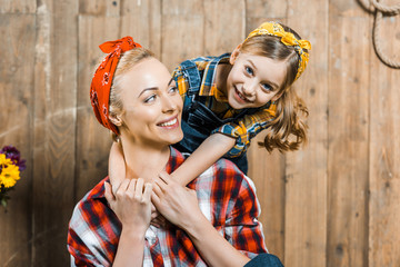 adorable daughter hugging cheerful mother near wooden fence