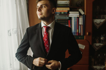Handsome groom in white shirt with red tie buttoning up black suit, morning wedding preparation, businessman in suit looking out the window