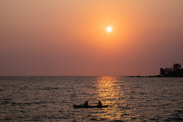 silhouette of a couple on kayak on the sea at sunset
