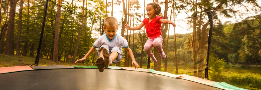 Little child enjoys jumping on trampoline - outside in backyard