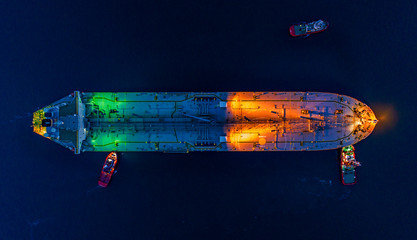 Aerial view oil tanker ship at the port at night, import export business logistic and transportation.