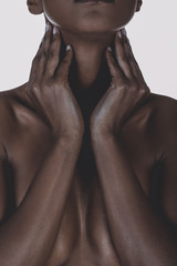 Statuesque cleavage of nude black mixed race woman covering breast.