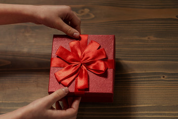 gift untiechildren's hands untie the bow on the gift box on wooden background, top view. Red box, red bow.