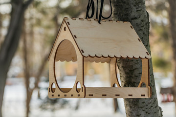 A beautiful new yellow bird and squirrel feeder house from plywood is on a black rope on a brown tree in a park in winter